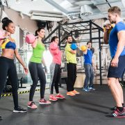 Men and women with coach at kettlebell functional training in fitness center